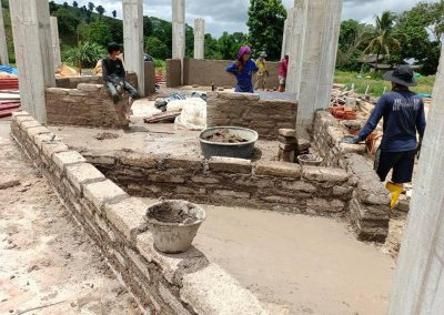 Photo of workers starting to lay brick on walls